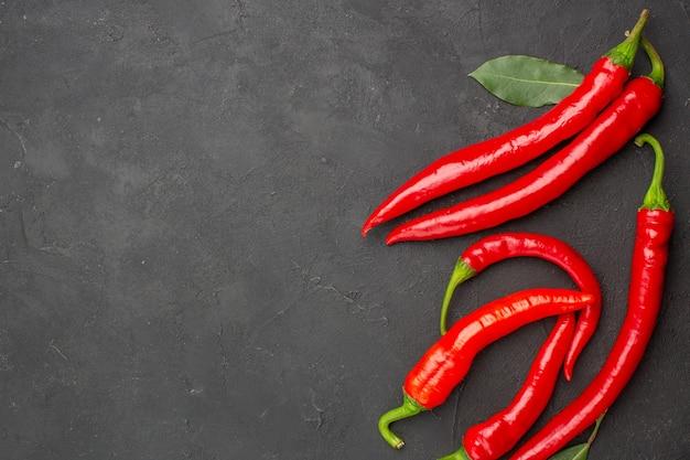 Bovenaanzicht rode paprika's en loonblaadjes aan de rechterkant van de zwarte tafel met vrije ruimte