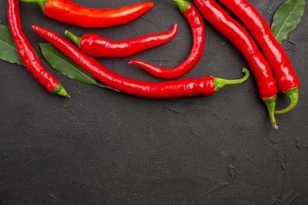 Bovenaanzicht rode paprika's en loonblaadjes bovenaan zwarte tafel met vrije ruimte