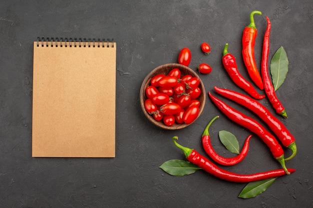 Bovenaanzicht rode paprika's en loonblaadjes en een kom met kerstomaatjes en een notitieboekje op zwarte tafel