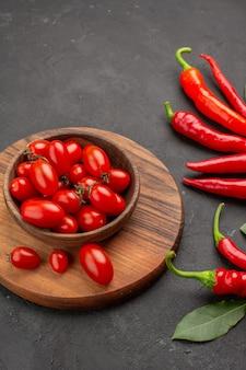 Bovenaanzicht rode paprika's en loonblaadjes en een kom met kerstomaatjes op het snijbord op zwarte tafel met vrije ruimte