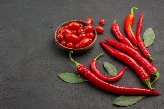 Bovenaanzicht rode paprika's en loonblaadjes en een kom met kerstomaatjes op zwarte tafel met vrije ruimte
