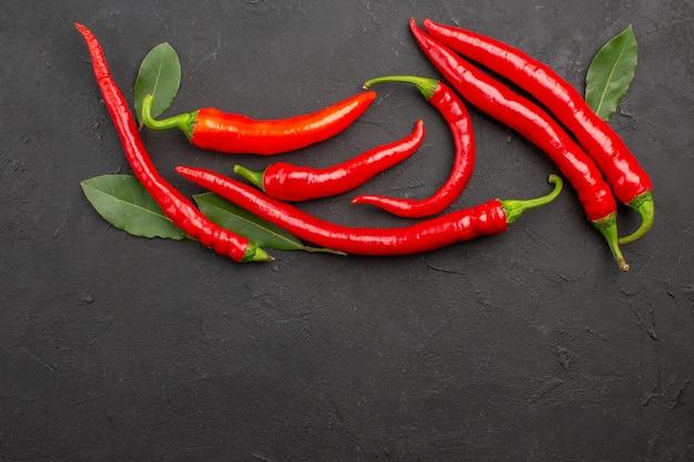 Bovenaanzicht rode paprika's en loonblaadjes op zwarte grond met vrije ruimte