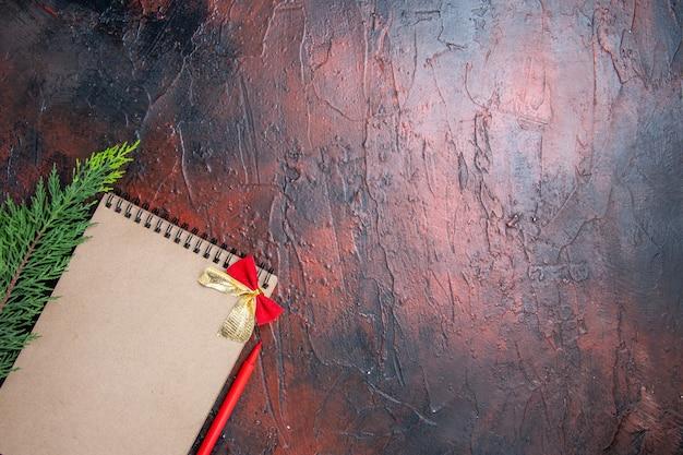 Bovenaanzicht rode pen een notitieblok met een kleine strik een dennentak linksonder op een donkerrood oppervlak met kopie ruimte