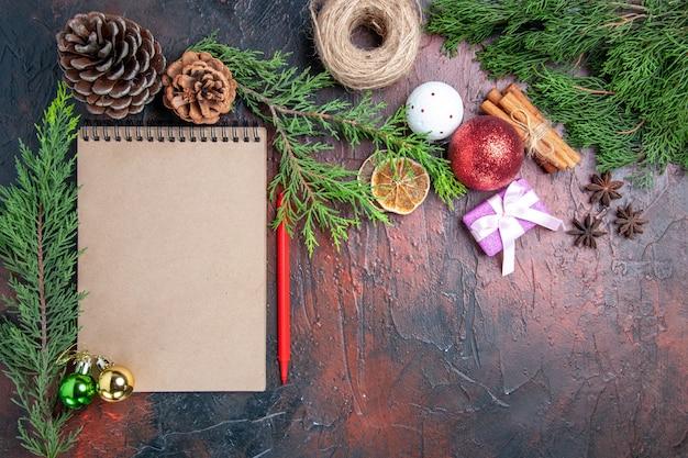 Bovenaanzicht rode pen een notitieboekje pijnboomtakken kerstboom bal speelgoed en cadeau kaneel anijs stro draad op donkerrood oppervlak vrije plaats