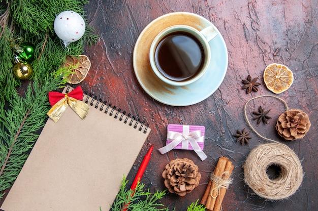 Bovenaanzicht rode pen een notitieboekje pijnboomtakken kerstboom bal speelgoed stro draad steranijs kopje thee op donkerrood oppervlak kopie ruimte