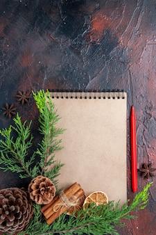 Bovenaanzicht rode pen een notitieboekje pijnboomtakken steranijs gedroogde schijfjes citroen op donkerrood oppervlak kopie ruimte