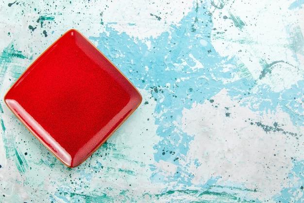Bovenaanzicht rode plaat vierkant gevormd leeg op blauwe achtergrond