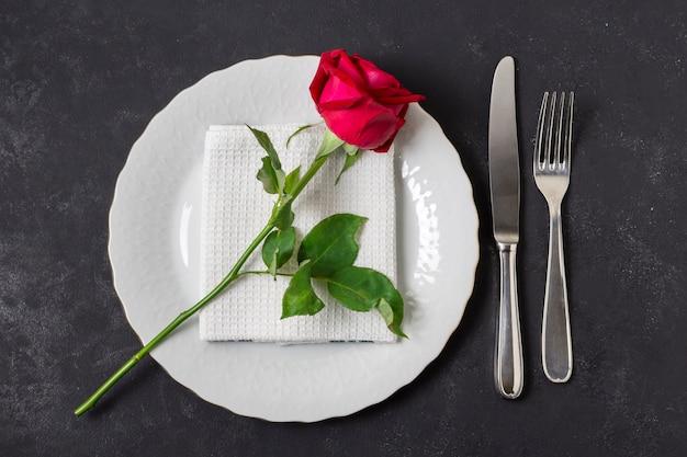 Bovenaanzicht rode roos op een bord met bestek