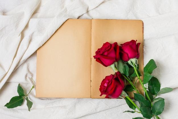 Bovenaanzicht rode rozen bovenop een boek