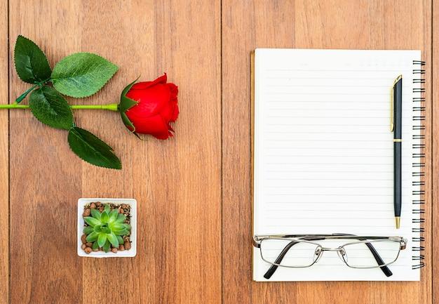Bovenaanzicht rode rozen op houten tafel en pen op kladblok op houten dek, valentijnsdag concept