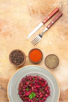 Bovenaanzicht rode salade gemengd met groene bladeren met zwarte peper, gemalen zwarte peper en kurkuma op lichte houten tafel met vrije ruimte voor tekst