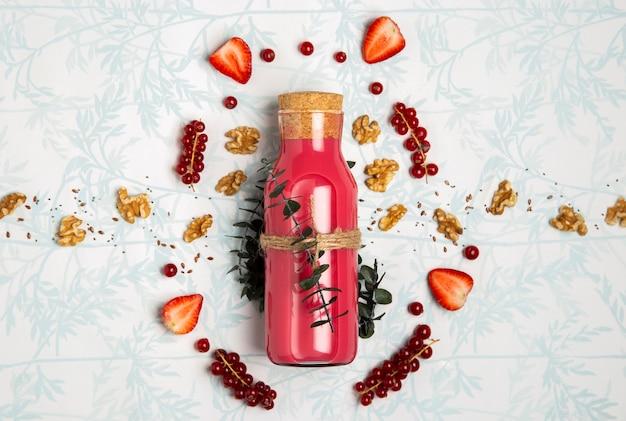 Bovenaanzicht rode smoothie met noten zaden en aardbeien