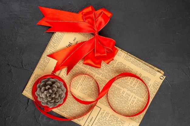 Bovenaanzicht rode strik lint dennenappel op krant op donkere ondergrond