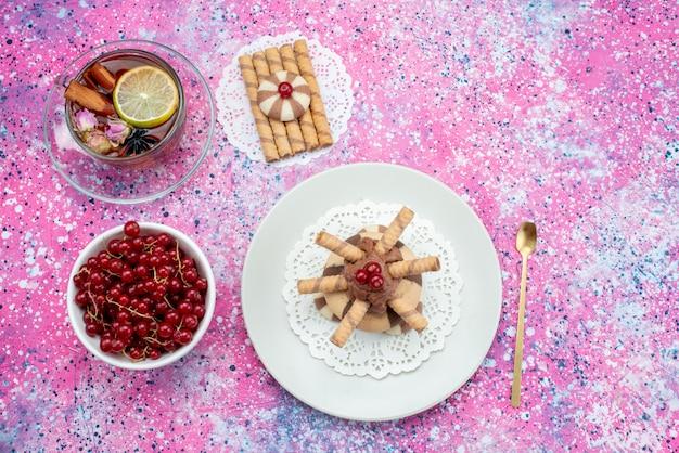 Bovenaanzicht rode veenbessen met thee en koekjes op de paarse backgorund koekjesfruit suikerkleur