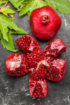 Bovenaanzicht rode verse granaatappel met groene bladeren op het donkere oppervlak