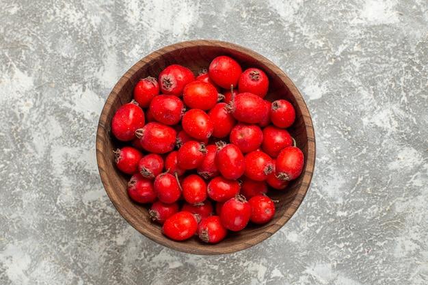 Bovenaanzicht rode vruchten in plaat op witte achtergrond