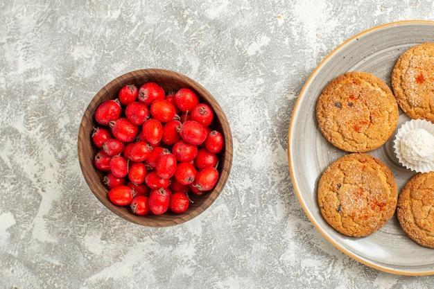 Bovenaanzicht rode vruchten met koekjes op witte achtergrond