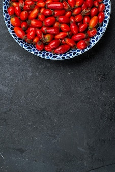 Bovenaanzicht rode vruchten rijpe en zure bessen binnen op grijs oppervlak