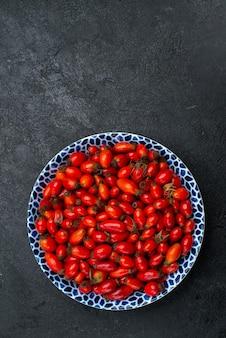 Bovenaanzicht rode vruchten rijpe en zure bessen op grijze ondergrond