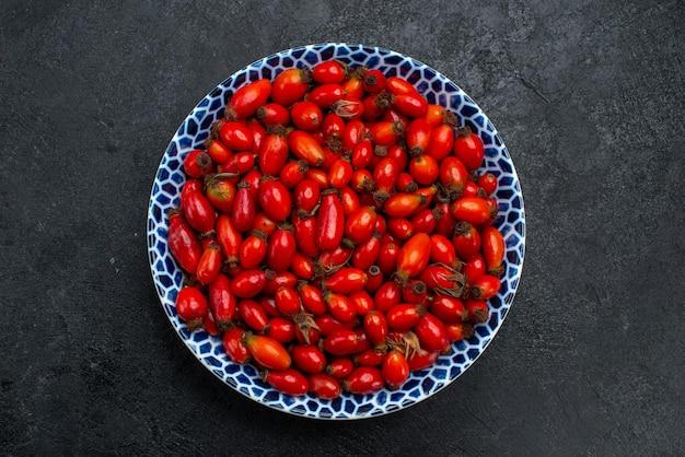 Bovenaanzicht rode vruchten rijpe en zure bessen op het grijze bureau