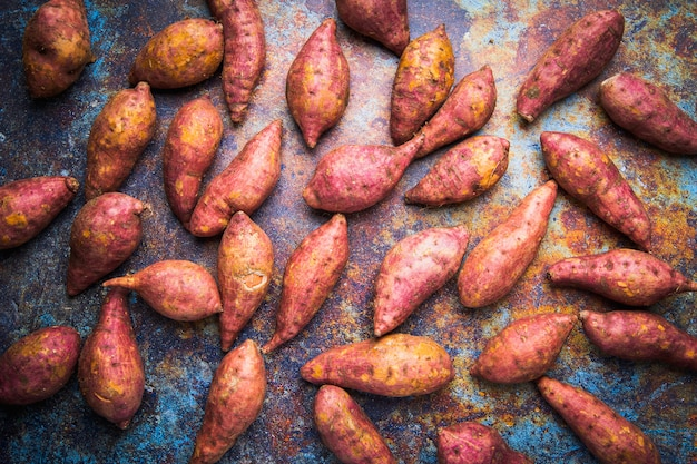 Bovenaanzicht rode zoete aardappelen, rauwkost display op grunge metalen achtergrond
