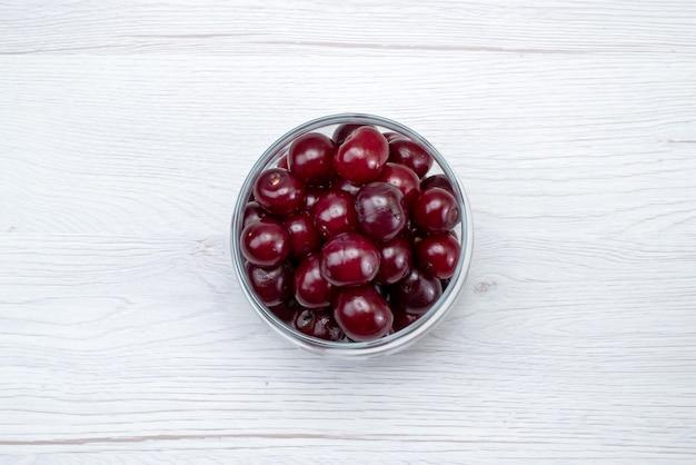Bovenaanzicht rode zure kers vers geheel en zacht op de lichte achtergrond fruit frisse kleur zuur zacht sappig