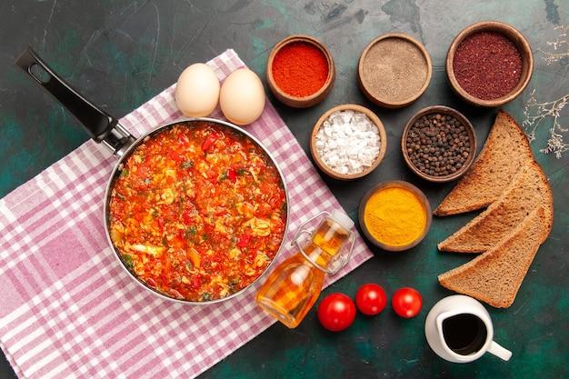 Bovenaanzicht roerei met tomaten en verschillende kruiden op het donkergroene bureau