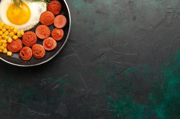Bovenaanzicht roerei met worst en groenten op het donkergroene bureau