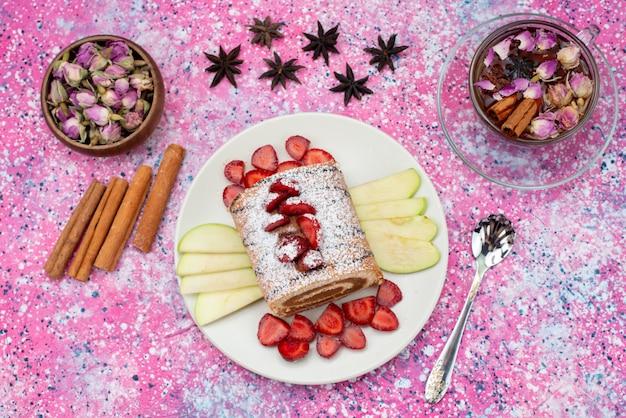 Bovenaanzicht roll cake in plaat met appels en aardbeien samen met kaneel en thee op de gekleurde achtergrond cake bak zoet fruit
