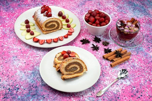 Bovenaanzicht roltaart in bord met appels en aardbeien, samen met kaneel en thee op het helderpaarse bureaukoekkoekje met zoet fruit