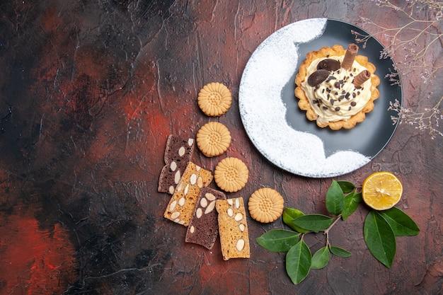 Bovenaanzicht romige cake met koekjes en plakjes taart op donkere tafel zoete cake dessertsuiker