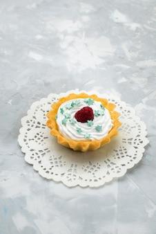 Bovenaanzicht romige cake met stersuikergoed en framboos op het grijze zoete oppervlak