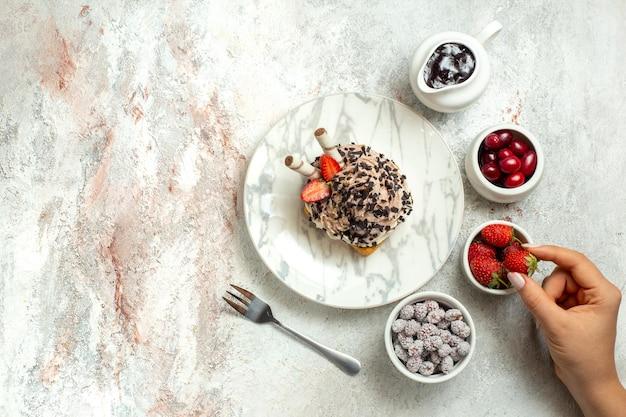 Bovenaanzicht romige heerlijke cake met aardbeien en snoepjes op wit oppervlak verjaardag cream tea cake biscuit zoete cookie