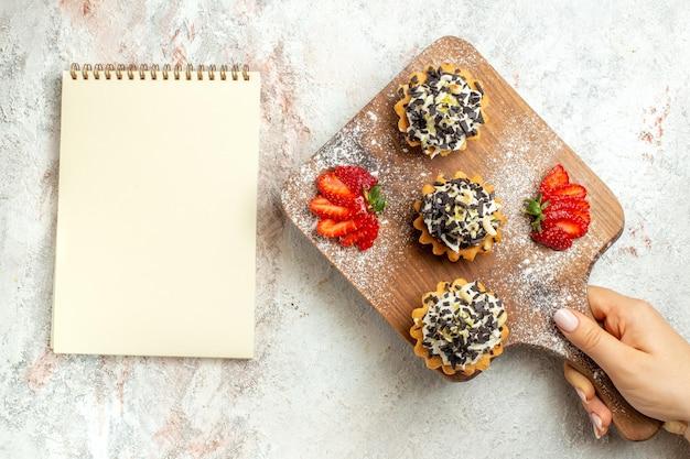 Bovenaanzicht romige heerlijke taarten met gesneden aardbeien op witte oppervlakte cream tea cake biscuit verjaardag zoet