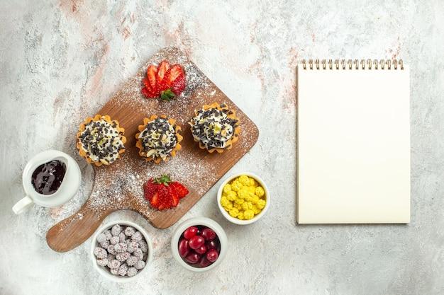 Bovenaanzicht romige heerlijke taarten met gesneden rode aardbeien en snoepjes op witte oppervlakte cream tea cake biscuit verjaardag zoet