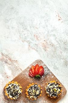 Bovenaanzicht romige heerlijke taarten met gesneden rode aardbeien op witte oppervlakte thee cake biscuit verjaardagscrème zoet
