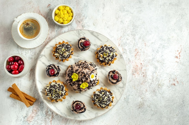 Bovenaanzicht romige heerlijke taarten met kopje koffie op witte oppervlakte thee cake biscuit zoete verjaardagscrème