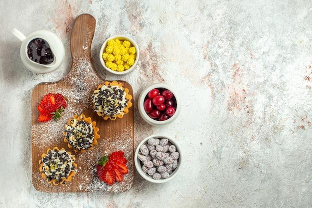 Bovenaanzicht romige heerlijke taarten met rode aardbeien en snoepjes op witte oppervlakte thee cake biscuit zoete verjaardagscrème