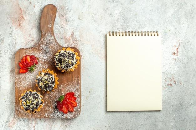 Bovenaanzicht romige heerlijke taarten met rode aardbeien op witte oppervlakte thee cake biscuit zoete verjaardagscrème