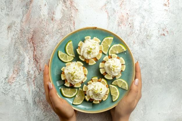 Bovenaanzicht romige heerlijke taarten met schijfjes citroen op licht wit oppervlak cake biscuit cookie cream tea sweet