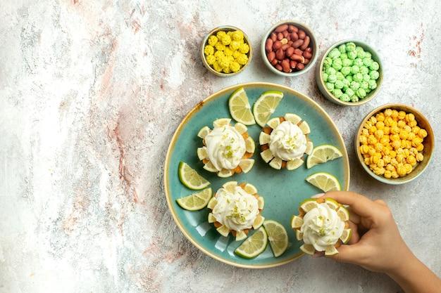 Bovenaanzicht romige heerlijke taarten met schijfjes citroen op wit oppervlak cake biscuit cookie cream tea sweet