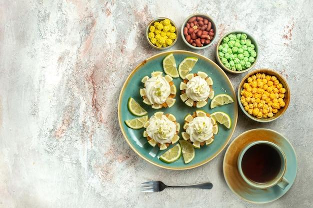 Bovenaanzicht romige heerlijke taarten met schijfjes citroen op witte desk cake biscuit cookie cream tea sweet