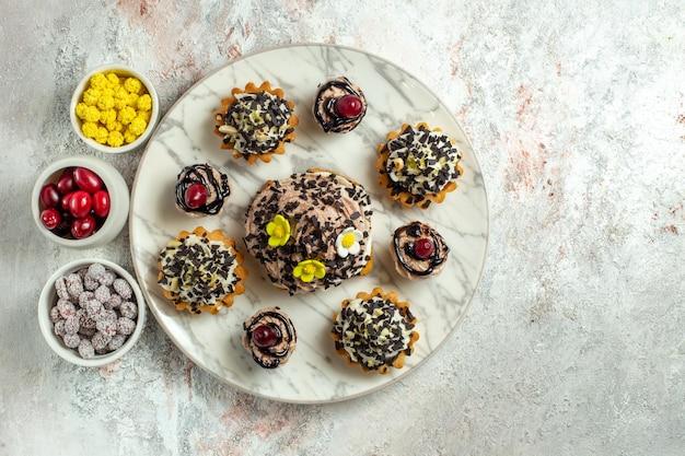 Bovenaanzicht romige heerlijke taarten met snoep op witte oppervlakte thee cake biscuit zoete verjaardagscrème
