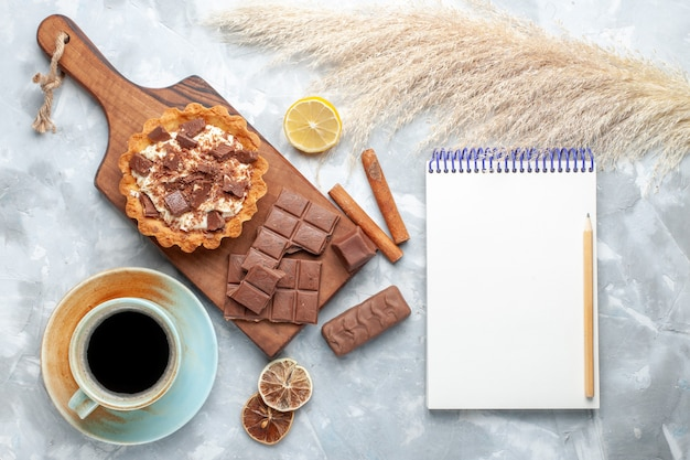 Bovenaanzicht romige kleine cake met chocoladerepen blocnote en kaneel op licht bureau zoete cake crème chocolade