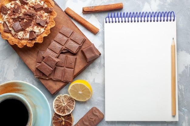 Bovenaanzicht romige kleine cake met chocoladerepen blocnote en kaneel op licht bureau zoete cake suiker crème chocolade