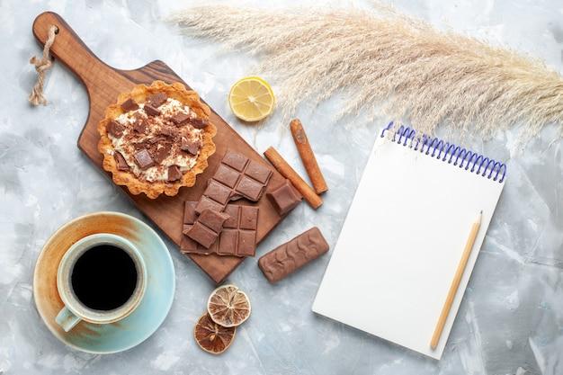 Bovenaanzicht romige kleine cake met chocoladerepen thee blocnote en kaneel op licht bureau zoete cake suiker crème chocolade