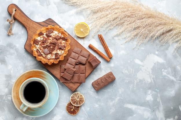 Bovenaanzicht romige kleine cake met chocoladerepen thee en kaneel op licht bureau zoete cake suiker crème chocolade