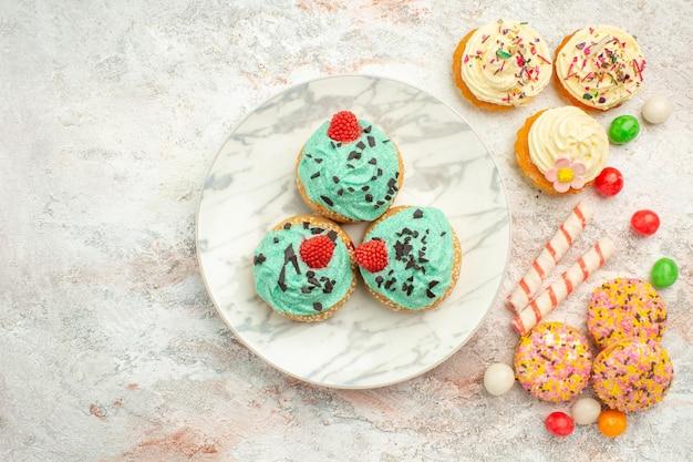 Bovenaanzicht romige kleine taarten met koekjeskoekjes op witte oppervlaktecrème dessertkoekjestaart