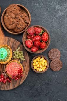 Bovenaanzicht romige taarten met fruit en koekjes op donkere tafel dessert koekje zoet