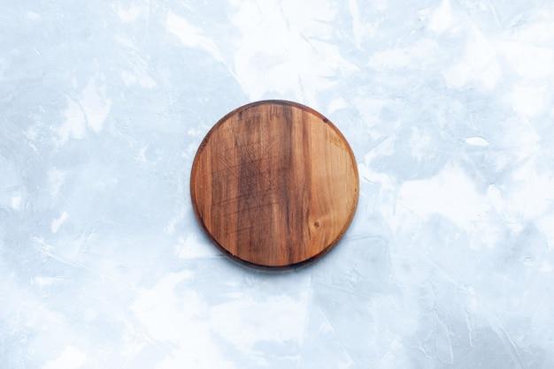 Bovenaanzicht rond bruin bureau gemaakt van hout op het lichte houten houten bureau van de achtergrondkleurfoto